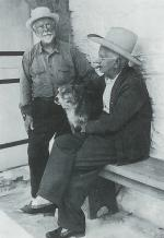 A black and white photograph of George Landis standing and Henry sitting. Henry sports a cow boy hat and is smoking a stogie, while his arms surround the family dog.