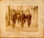 Men walk down a city street. Left to right:  George W. Harltein, (Secretary, District 9) John Mitchell, Mr. Barrett (Reporter, Scranton Truth) May 7, 1902.