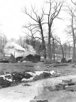 Shacks with billowing smoke stacks and stacks of wood. Snow on the ground and frozen creek bed.