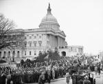 Photograph shows the huge army in front of the capitol as they demanded relief, flag in crowd, side view.