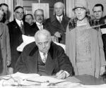 William Vare sits at a desk, pen in hand, while others stand behind him appearing to be awaiting his signature.