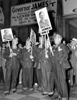 Men in overalls and miners hats with lights, hold signs that read James for President