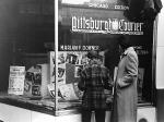 Photograph of a window of the Pittsburgh Courier and a woman and child look inside.