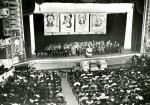 Interior photograph of an auditorium where a large group has gathered. On the stage a panel of men and women sit at a long table and above hangs a banner of black heroes.