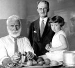 This publicity photo shows Philadelphia Mayor J. Hampton Moore peeling a potato, as Ernest Gray, age 81, and  Jean Helmstreet, age three pose next to him, at the Shelter for Homeless Men kitchen.