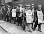 Marching strikers wear placards that read Municipal Wor