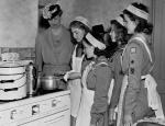 Four girl scouts gather around a stove. One stirs something in a pan as Eleanor Roosevelt stands nearby looking on.
