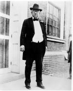 Photograph of John Wanamaker standing, wearing a tuxedo with tails, bowtie, and hat.