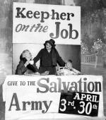 An elderly lady sits holding a cup, a seated, young boy, takes a bite of food. A salvation army worker stands between them with outstretched arms, her hands touching a shoulder of each. All are inside of a booth that has two signs. One sign reads: Keep her on the Job and the other reads: Give to the Salvation Army, April 3rd 30th .