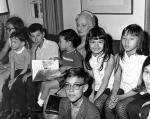 An elderly lady sits on a couch as she reads a book to a group of children surrounding her. A young boy is sitting on her lap.