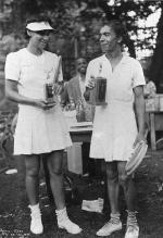 Two women dressed in tennis garb hold trophies.