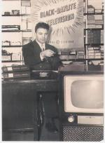 John Walson sits at his desk, in front of a General Electric sign that reads, Black-Daylite Television, as he points to a television directly in front of the desk. Small boxes are on shelving in the background.