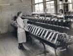 Two young women standing in front of machines in a silk mill factory wind the silk around their hands.'