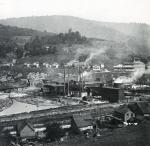 Distant view of the lumbering buidlings and logs in the water of the town. In the center of the photograph one can see the factory with billowing smoke rising in to the air and along the outskirts sit the houses.