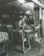 American Sheet and Tin Plate Company worker trims tin plate. '