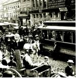 Horse-drawn wagons and carriages, an electric trolley car, and pedestrians congest a cobblestone Philadelphia street.