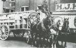 A wagon with a H. J. Heinz with open rails is loaded with barrels. A driver sits atop the wagon in a seat and holds the reins of three horses, two black, on each side of a white horse that is harnessed in the center.  The wagon is parked outside of the H.J. Heinz company.