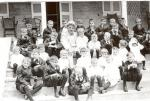 Milton S. Hershey and Industrial School students sitting on steps of Homestead; one boy sitting on his knee; formal portrait.
