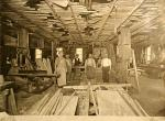 Interior photgraph of the carpentry shop and six make workers posing for the photo.