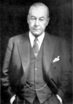 Balck and white image of a man, wearing a suit, standing with his hands in his pockets.