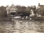 Crew team, 1904, preparing to put shell into Schuylkill River in front of boathouse.