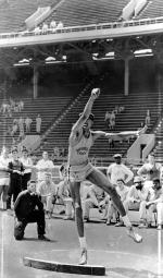 Wilt Chamberlain shooting the shot put.