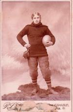 A young man in a uniform posing with a football in his hand.