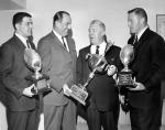 Art Rooney receiving the Bert Bell Man of the Year Award. Four men dressed in suits and holding trophys pose for picture.