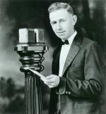 A man dressed in a suit stands at a microphone.