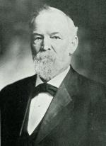 Head and shoulders image of a man in a suit.