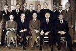 Two rows of people, the first one seated, consisting of 12 men, one male priest, and one female, pose for this group photo.