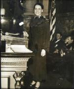 A woman standing in front of a podium, holding a gavel in her right hand poses for this photo. Men are seated behind her.