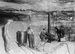 Three men and one male child are at work inside of a mine.