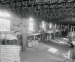 General view of the sled makers' production line.  The sled racks are overhead. The sleds are assembled in this room and passed along the line for their varnish bath.