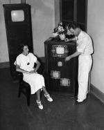 Mabel Bernstein watches as Philo T. Farnsworth tunes the combination radio and television receiving set.