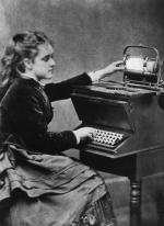 A young lady, wearing a long skirt and a long sleeve jacket, sits at a typewriter.
