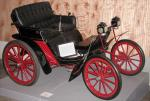 Color photograph of a black Duryea with read trim and red spokes.