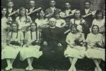 Joseph Murgas seated with a group of young parish girls wearing white dresses. Five men line the back row of this photograph.