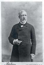 Albumen silver print of James Gillespie Blaine, ¾ length, right hand tucked inside of coat.