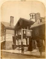 """The building on street, surrounded by other buildings. Two men standing in front, leaning against a signpost. Horse in lower right-hand corner. Signs: """"G. Goebel's Hotel and Lager Beer Saloon"""" ; """"Wrigley's Hotel."""""""