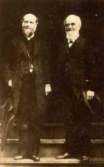 Two men in suits, standing side by side at an entranceway, pose for this full length portrait. '