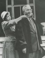 A man dressed in a business suit and a commencement gown stands while his wife stands behind him, adjusting the neck of the robe.