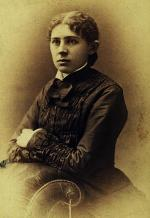 Sepia colored photograph of Ida Tarbell, leaning against the back of a chair.