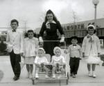 Image of young mother pushing a stroller carrying twins, while two young boys and two young girls dressed in their Easter clothes walk beside her. Woolworth's can be seen in the background.