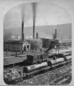 An image of a refinery with several large oil tanks, smokestacks, and railroad tracks in the foreground.