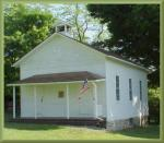 Exterior view of white one-room school house complete with flag and a bell.'