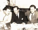 Three men sit at a table. Let to right, Hemingway, Billingsly, and O'Hara