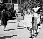Women demonstrate carrying placards Image right: a crowd gathers