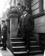 Tener exiting a building, walking down a fight of stairs, dressed in a tuxedo and top hat. Several men follow behind him and a door man stands along the sidewalk.
