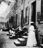 A street with row houses. Children and women sit on the steps or stand in the street